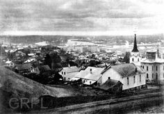 View of downtown with E. Bridge St in the foreground, now Michigan St NE - c. 1870