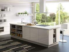Un îlot central comportant un plan de travail, une table de cuisson et un évier et d'étagères pour accueillir la vaisselle
