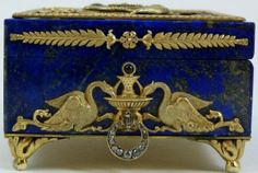 RUSSIAN SILVER & LAPIS JEWELED ENAMELED BOX by FABERGE -Dated 1913 on top. Has guilloche blue enamel design to top embellished with a double headed eagle crest design and encircled by a figural snake frame. Clad Griffin design to front. Dragon design to sides with jeweled handles and cabochon sapphire set. Has diamond set latch. Set on 4 scrolled feet. Faberge, 84 silver purity and town marks to bottom. Hold the Anders Juhaninpoika workmaster marks (Finnish, 1858-1933).
