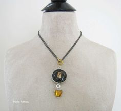 A classy and unique Champagne necklace that can be worn long or short. It's all about combination. Two black MUMM NAPA champagne caps are welded together back to back. Under the champagne caps hangs a pretty gold colored Venetian glass heart.