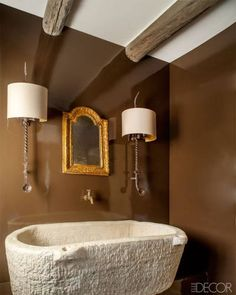 A powder room's stone sink and brass faucet are antique, the circa-1730 giltwood mirror is Spanish, and the sconces are by Restoration Hardware.