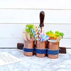 Repurpose some old tin cans, jeans and screwdriver into this useful stylish copper and denim caddy. What you need : 6 Tin Cans Hems of Old Jeans Old wooden hand…