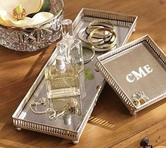 Mirrored Dresser-Top Trays  - With their antique mirrored bases and antique silver finish, these trays are a polished way to display items that accumulate on a desk or vanity – from jewelry and glasses to letters and watches. Edged with a pierced metal fretwork, both stand on ball feet and have black velvet backing.  #potterybarn #bebetsy #contest
