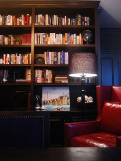 Cozy Library Nook    Black shelving and a bold red leather chair bring a sense of drama in this cozy library nook. Designer Jennifer Charleston occupied a corner of the dining room to allow guests to wind down after a big meal.… more