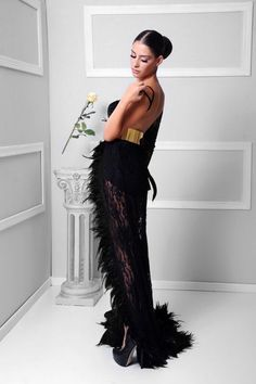 A black velvet gown covered with dentelle and feathers . And a gold metal belt #jczakaria #couture