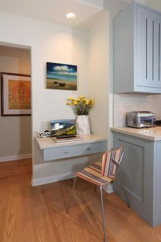 A floating desk drawer provides a handy corner for paying bills or reading recipes in this small kitchen office nook. The desk is painted the same cool blue as the kitchen cabinets with a multicolored striped chair adding extra color to the space.