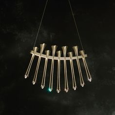 ARTEMIS LED PENDANT Elegance with an edge — bold sculptural quills of forged steel with tines grasping Swarovski Boomerang crystals create this distinctive and powerful pendant.