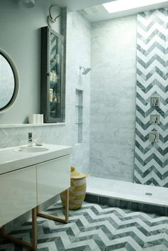 Stunning bathroom with open shower featuring skylight, marble niche with glass shelves, stacked marble tile, black and white chevron tiled wall and mosaic marble shower floor.