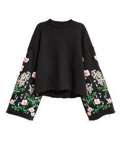 Svart/Blommig. En tröja i mjuk sweatshirtkvalitet. Tröjan har nedhasad axel och lång trumpetärm med broderier. Råa kant nedtill och vid ärmslut.