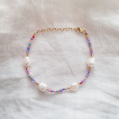 Introducing the Ocean Treasure Bracelet featuring 4 White Baroque freshwater pearls at 8×9mm approximately detailed in Gold seed beads and beautiful colorful glass seed beads. Wear alone or layer it for the ultimate effortless chic look!