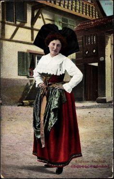 Elsässische Frau in Tracht posierend, Haus