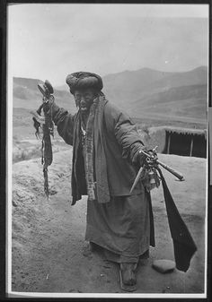 Bonpo lama with protruding tongue holding trumpet, dagger, and bell and drum, chopper, and hair of  100 dead  and 100 living people  in a state of trance on the roof of Joseph Rock's quarters at Radja Lamasery. dated July 11, 1926: