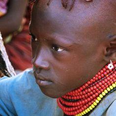 Akina tiene 13 años, vive en Turkana, en la frontera con Etiopía.  El día que fue tomada esta foto, toda la tribu estaba reunida, ya que un pequeño equipo médico estaba revisando el peso de los niños más pequeños, para controlar la desnutrición y poder tratarla a tiempo.  A Akina ya no le tocaba el control, pero no apartaba la mirada de unas enfermeras que pesaban a un niño cerca suyo. Su mirada era la de alguien que está viendo, algo nuevo y concentrada se imagina que ella es la enfermera.