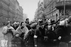 Jews are gathered at the intersection of Karmelicka and Nowolipki Streets in the Warsaw ghetto