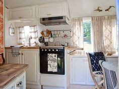 white cabinets, black stove, wood counter.