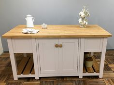 Freestanding kitchen island incorporating two back-to-back double cupboards & slatted end shelves at both ends. Made in 4 Parts (plus worktop) it will fit through any standard width doorway for easy re-assembly once in place. Here the island is fitted with a 40mm thick Oak Worktop but other hardwood options are available. Shown here finished in Farrow & Ball 'Peignoir' but any size or colour can be made to order. Size Shown L:1800mm x H:910mm D:960mm