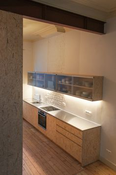 Atelier Antipode | OSB kitchen and cabinet dividing the entrance from the living space
