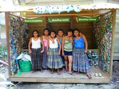Bottle Brick Bodega | GUATEXPERIENCE - local young ladies in the 3-section bottle brick station. People can leave trash for fill, empty bottles, and drop off completed ecoladrillos. Presumably if you don't have bottles or trash, you can take it from the center and return it when you've completed the brick.
