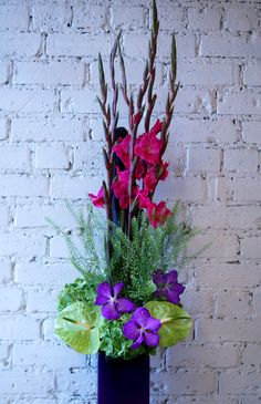 A beautiful arrangement featuring cerise gladioli, purple vanda orchids, green anthurium, green hydrangea and thlaspi green bell. #reidsflorists #corporateflowers #summerflowers