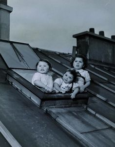 Three of Salkazanov's little children looking at the sky from the window of their little garret, 1950, Robert Doisneau.