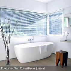 Ein Platz zum Entspannen und Erholen: Die freistehende Badewanne in dem natürlich eingerichteten Badezimmer ist extra am Fenster platziert, um den Ausblick in…
