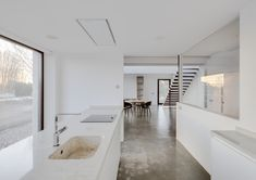 The concrete floors and white high gloss cabinetry offer a simple minimalist feel for this kitchen