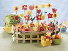 FLOWERING WATERMELON GARDEN Watermelons and pineapples sprout together to make this blossoming fruit garden. Serve it at any garden party for a fun and healthy part of your party decor.