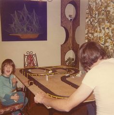 Slot car races on the kitchen table!     Slot cars are powered small vehicles that are assisted by a slot or groove set in the tracks on which they run. At the bottom of the car is a blade or pin that keeps the car in the slot. To make the car run, the metal strips placed next to the slot d