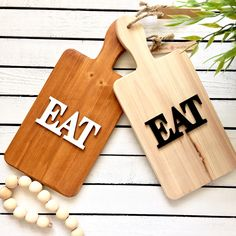 """The word """"Eat"""" atop a wooden cutting board. Hang this whimsical piece to bring a hint of farmhouse charm to your kitchen."""