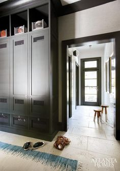 Brian Watford - Fabulous mudroom features black cubbies over black mudroom lockers stacked over chicken wire cabinets designated for shoes alongside walls lined with gray textured wallpaper framing doorway finished with black door moldings.