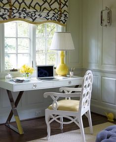 White and yellow office features gray paneled walls lined with a Jonathan Adler Channing Desk topped with a yellow lamp paired with a white Bungalow 5 Loop Arm Chair placed under a window dressed in a black and white roman shade in Zimba Charcoal Fabric.