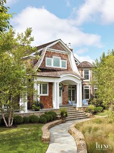 A curving New York-bluestone path leads to the home, which features a Dutch gambrel façade with low mounds of boxwood at the sides; divided-light windows showcase diamond detailing. Karney stone, a sedimentary rock from New Jersey hand-chipped and chiseled to fit, was used for retaining walls.