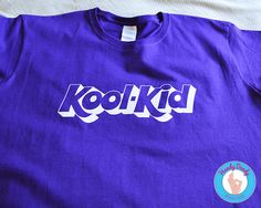 This fun t-shirt is exactly what you need to embrace your inner child. Our made-to-order shirt features the phrase Kool-Kid in a style that mocks the Kool-Aid logo. The artwork is white on a purple (or other color of your choosing) t-shirt. Check out our matching kids shirt here: https://www.etsy.com/listing/508469866/kool-kid-kids-shirt-cool-kid-onesie-kool?ref=shop_home_active_1  All of our products are made to order and we love customizing them especially for ...