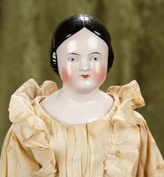 "19"" German porcelain doll with ringlet curls and nice antique costume ~~Porcelain shoulder head, black sculpted hair in short ringlet curls, lightly-tinted complexion, painted blue eyes, closed mouth, muslin stitch-jointed body with sewn-on stockings and leather boots, porcelain limbs, wearing antique gown and undergarments, Germany, circa 1860."