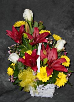 Red Lilies, Yellow Daisies and white Roses.