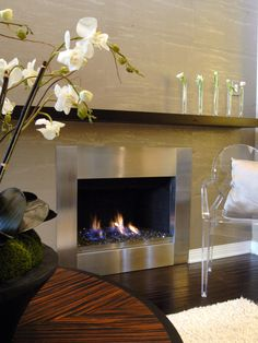 This neutral contemporary living room features a stainless steel fireplace with a floating mantel that stretches across the width of the wall. The mantel features five thin vases, each of which is filled with a single white flower. Modern Fireplace Mantles, Home Fireplace, Fireplace Remodel, Fireplace Surrounds, Fireplace Stone, Brick Fireplaces, Fireplace Update, Fireplace Ideas, Contemporary Fireplace Designs