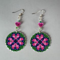 <p> Earrings adorned with my purple pansy and pink bleeding heart boho chic mandala new age sacred geometry hippie kaleidoscope charm titled Love Struck. These heart earrings are lightweight and dainty . Heart earrings begin with a dangle of dark moss green bicone Swarovski crystals and a fuchsia heart Swarovski crystal beads that accentuate the colors in the mandala charm...