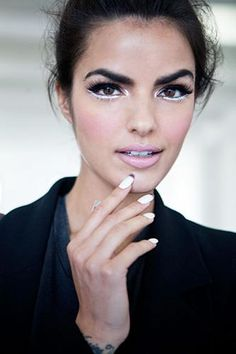 In this season. Bold brows, black and white, crazy long nails with nail tips. Beautiful eyes with bold black tops and white detailing. A little bit of 80s pink in the lips.