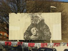 """This is an amazing and startling scene on Howard Street above North Ave. in the middle of used car lots and tinsel. The local mural artist gaia.streetart says """"this piece on Howard St is the rooster messenger cradling the head of St John as depicted  #gaia - More #streetart at www.Streetart.nl"""