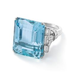 An aquamarine and diamond ring The rectangular cut-cornered aquamarine, approximately weighing between 30.00 – 35.00 carats, set to baguette- and single-cut diamond shoulders