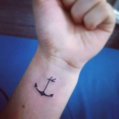Left inner wrist tattoo of an anchor including the word...