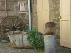 Un rincón con encanto ancestral..su bañera ,la rueda de un coche y gran champiñón de madera