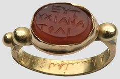 "Gold ring with gem, Roman, 1st / 2nd Century. AD Oval carnelian gem with happiness slinging ""EYTYKI"" inscription in Greek. Golden version, on the shoulder three golden ornamental beads."