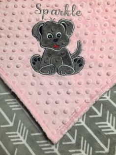 This Blanket is made with minky fabric on both sides. Personalize with a puppy appliqué and an embroidered name or initials.  The pictured blanket has blush pink dimple dot minky on one side and gray smooth minky with white arrows on the other side with a gray puppy appliqué and gray name. The blanket is handmade by me with premium, soft minky from Shannon Fabrics and is perfect for baby to snuggle. The blanket is top stitched for durability. This beautiful blanket would make a wonderful…