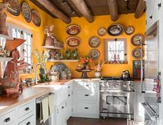 The Viking range, dishwasher and refrigerator complete this New Mexico kitchen Judith Espinar, Jim Deville and Scott Roberty. It's painted in a cheery, sunbaked yellow that's a perfect backdrop for pottery and folk art.