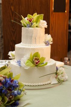 Light and delectable wedding cake made of fresh cream and beautifully adorned with green cymbidium orchids and sprigs of bear grass.  Photo by Geralyn Camarillo of Hokuli'i Images.