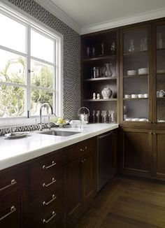 wood stained cabinets, chrome fittings, shelving over the depth of the counter, stainless sink, patterned black and white tile