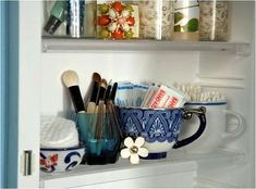 vintage tea cups as storage in your bathroom medicine cabinet. i have been using small jars and stem glasses on my sinktop, but this idea is cute too.