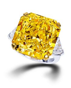 Yellow cushion-cut diamond ring with white pear-shaped diamond shoulders from Graff.