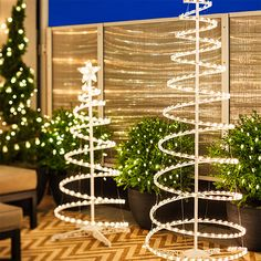Outdoor holiday lighting with white lighted spiral Christmas trees.